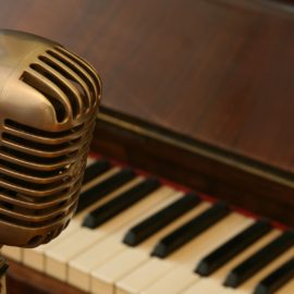 old style microphone and piano keys